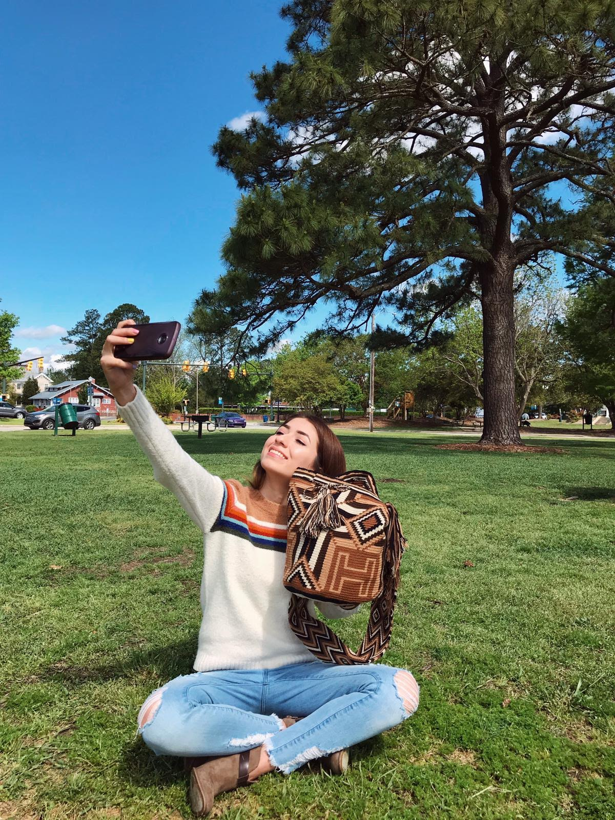 Young Woman Holds the Brown-Cross Wayuu Mochila Bag with a beautiful combination of the following colors: Beige, Light Brown, Brown, Dark Brown, and Black while taking a picture with her cell phone.