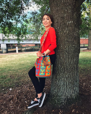 Young Woman Shows the colorful hieroglyphic Wayuu Mochila Bag with patterns in the following colors: Dark-Aquamarine, Orange, Orange-red, Light-Green and Rubine-red.