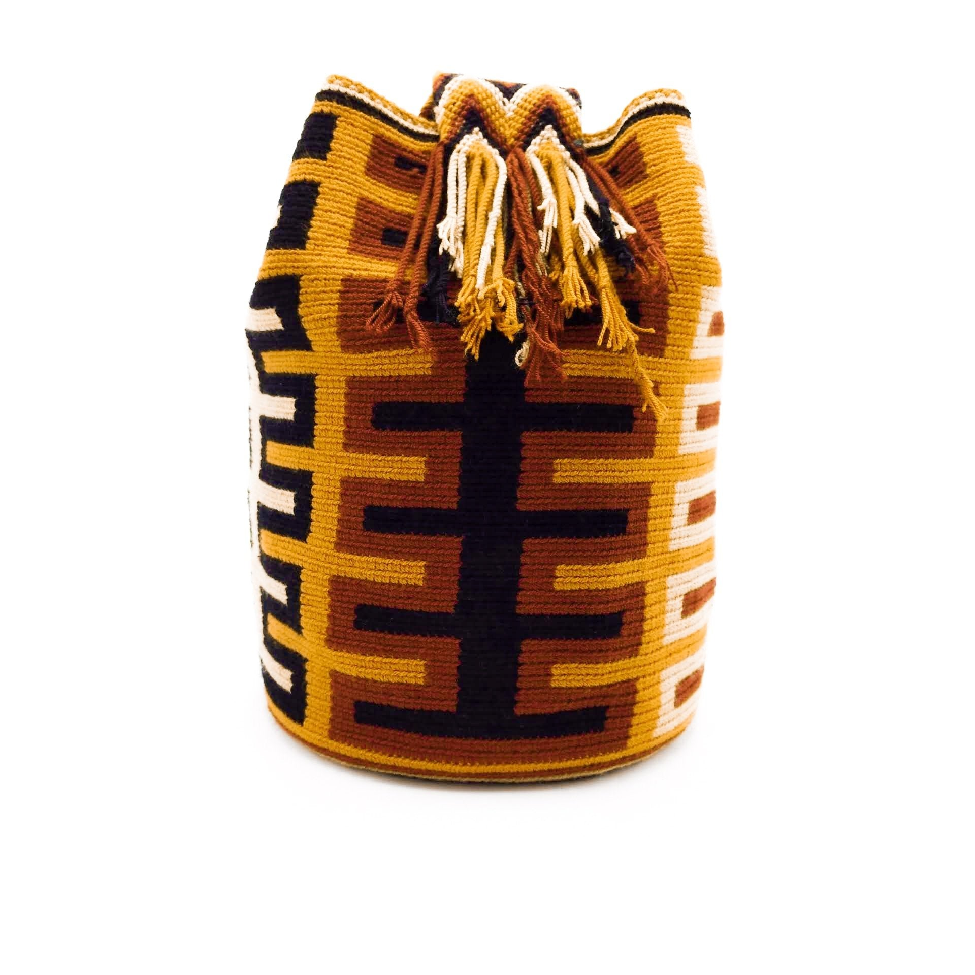 Side view of a pretty Wayuu Mochila bag with an awesome pattern in earthy colors such as Amber, Tan, Carmine, and Black