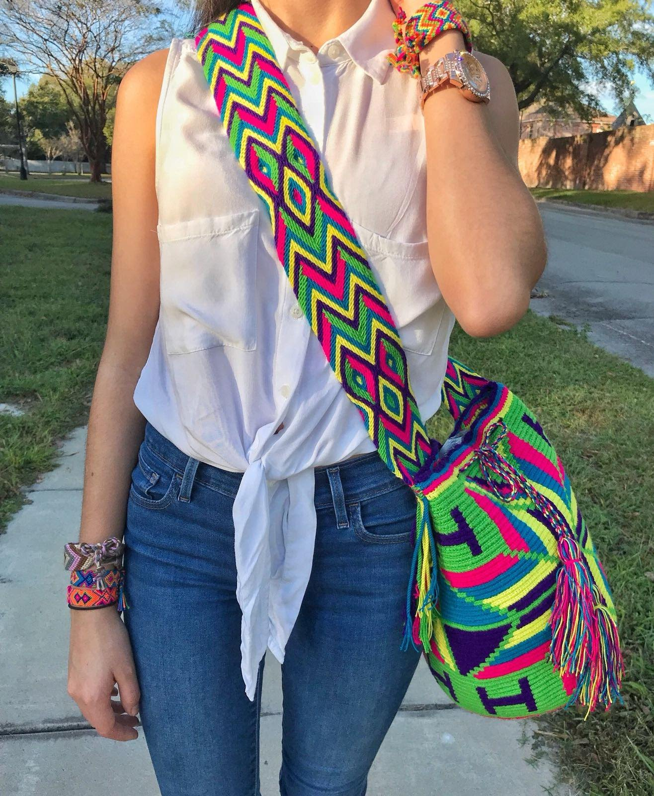 Young Woman Shows the Green Macaw Wayuu Mochila Bag with a beautiful arrays of the following vibrant colors: Light-Green, Cerulean (Dark-Aquamarine), Bright-Rose, Purple, and Yellow.