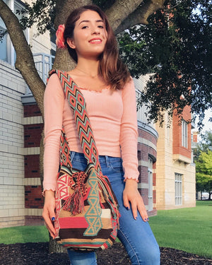 Young woman wears the beautiful Strawberry Cheese Cake Wayuu Bag.