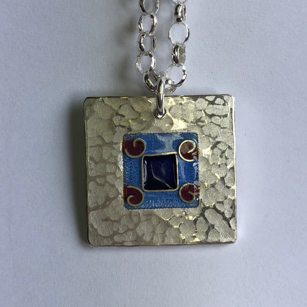 Pendant, blue on blue square with 4 red koru's