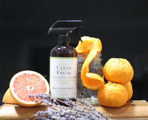 image of Red's Gone Green Grapefruit Orange Lavender All Purpose Cleaner sitting next to a grapefruit, oranges and a dried lavender bunch