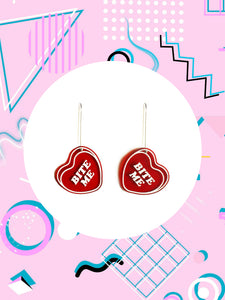 Red candy hearts earrings that say, bite me.