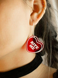 Woman wearing red dangle candy hearts earrings that say, bite me.