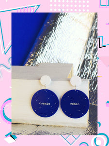 Dark blue circular earrings that feature memphis design elements and say, cosmic woman.