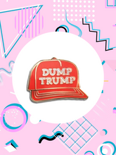 enamel pin shaped like a red snap back hat that says, dump trump