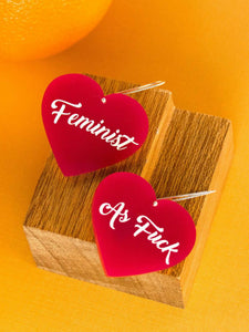 two heart shaped earrings on a wooden block, one says, Feminist, one says, As Fuck