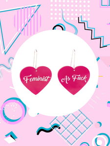 heart shaped left earrings says, Feminist, right heart shaped earring says As Fuck