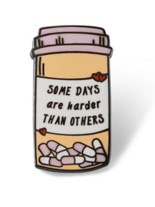 enamel pin shaped like a pill bottle says, some days are harder than others