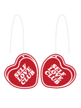 earrings that say SELF LOVE CLUB encased in transparent red candy heart