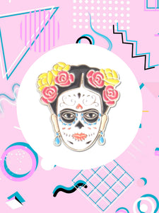 enamel pin shaped like Frida Kahlo's face wearing Day of The Dead makeup