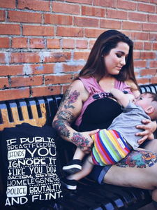 woman breastfeeding while holding a black cloth tote that says, If public breastfeeding offends you ignore it like you do racism sexism homelessness police brutality and flint
