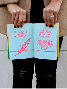 manicured hands holding book open to page inside that says, be gentle with yourself