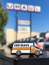 enamel pin shaped like a u-haul that says, she-haul