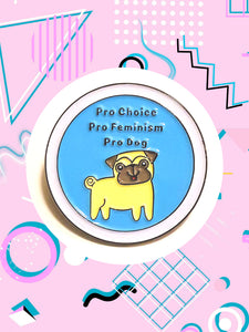 round enamel pin featuring a cartoon dog that says, pro choice pro feminism pro dog.