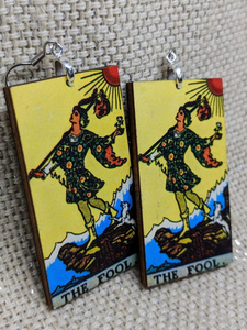 Lightweight rectangular wood earrings painted to resemble the fool card from the Rider Waite tarot deck.