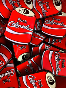 pile of enamel pins shaped like a can of soda pop that says, fuck colonialism
