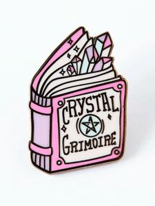 enamel pin shaped like a book called crystal grimoire with crystals peeking out the top