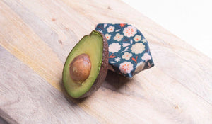 Mini reusable beeswax wrap keeping half an avocado fresh
