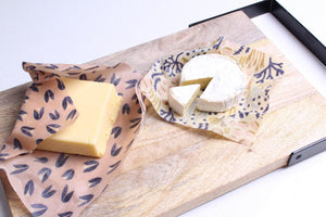reusable beeswax wraps on chopping board keeping cheese fresh