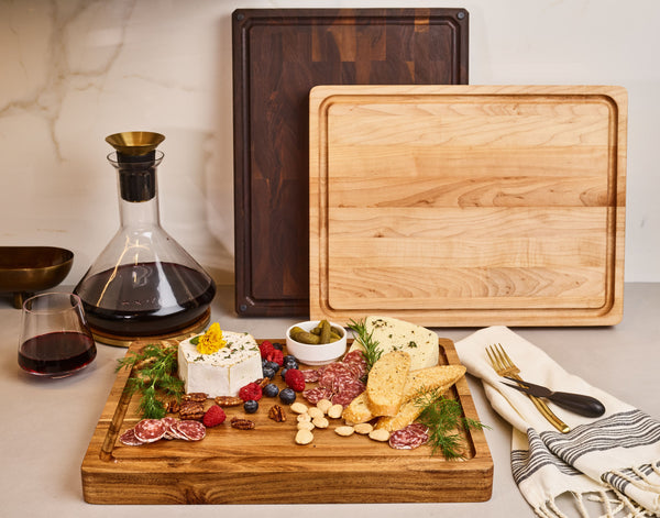 Cheese and meat charcuterie displayed on a beautiful acacia wood cutting board with a glass of wine in the back.