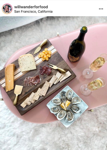 Crackers and cheese spread on a walnut wood cutting board with champagne and oysters