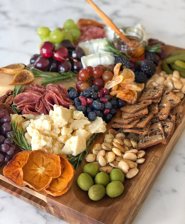 Beautifully styled charcuterie board with dried persimmons, olives, pistachios, crackers, salami, cheese, grapes and more.