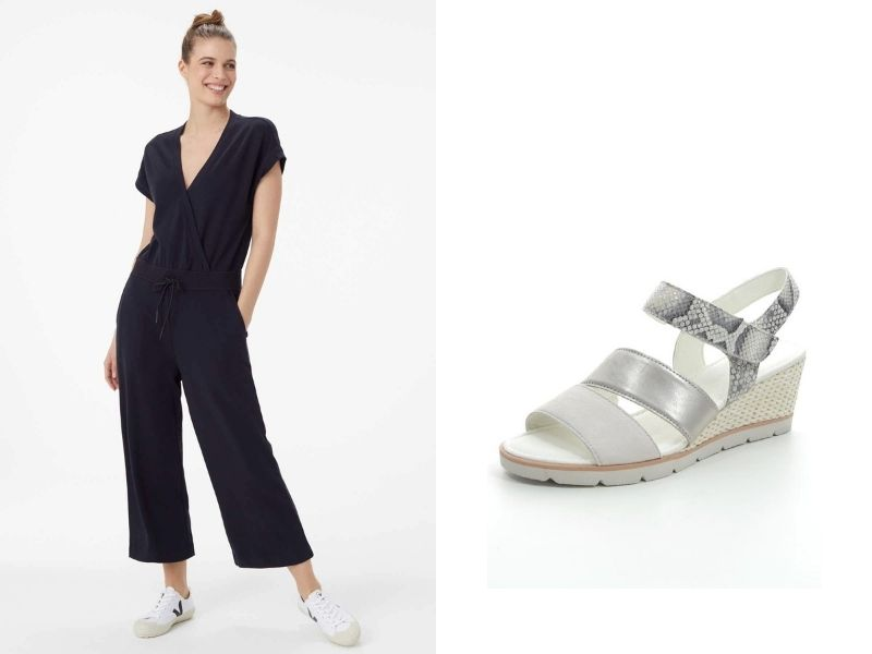 Lolë Flat Track Long One Piece is shown in black. The legs are wide, with a slight flare, and come above the ankle. They are shown with Gabor Poem Wedge sandals, in metallic silver and snakeskin leather with a wedge heel. The sole and heel are white.