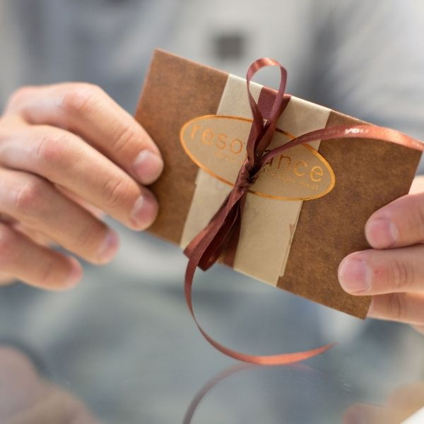 A man holds a decorated envelope. It is wrapped in brown and bronze paper and has bronze ribbon.