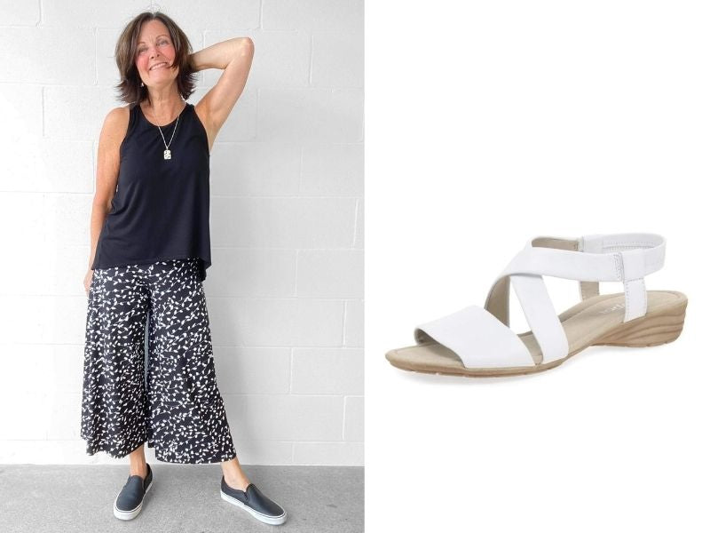 Miik wide leg pants have a black background and a small white floral print. Strappy Gabor sandals are made of white leather and a slightly raised heel.