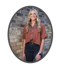 In the photograph, a woman stands against a brick wall, smiling at the camera. She wears a rusty brown blouse with short sleeves, and black jeans. She's also wearing a chunky watch.