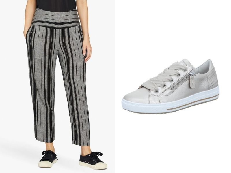 Masai Panna Trousers have a wide waistband and a loose leg. They have charcoal and black vertical stripes and come to just above the ankle. They are shown with Gabor sneakers in metallic silver. The sneaks have a thick white rubber sole and a zipper detail on the outside of both feet.