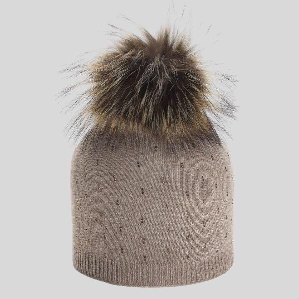 A beige hat is shown, with tiny rhinestones on the body of the hat, and a fur pompom on top.