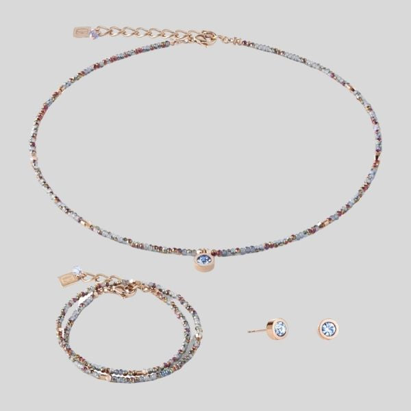A delicate necklace, bracelet and earrings are shown.