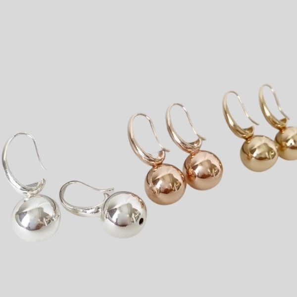 Three pairs of earrings are shown. They are small metallic balls. One pair is silver, one pair is rose gold, and one pair is gold.