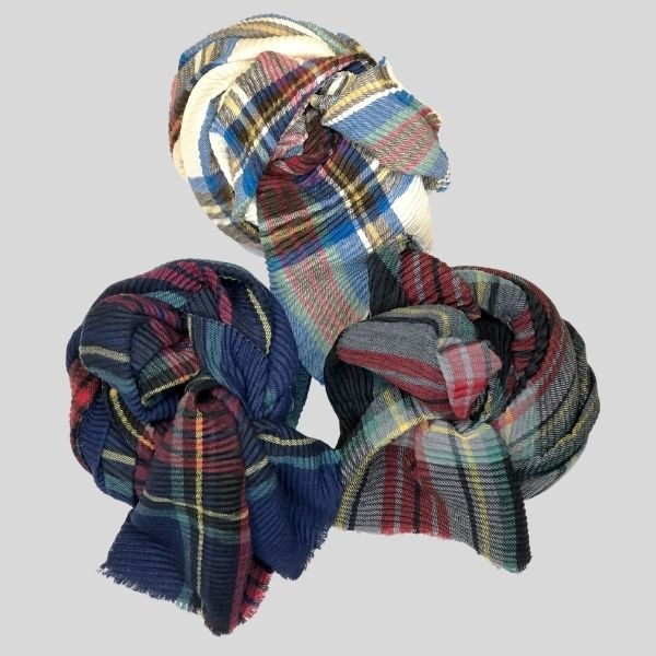 The image shows three plaid scarves rolled into cute balls.