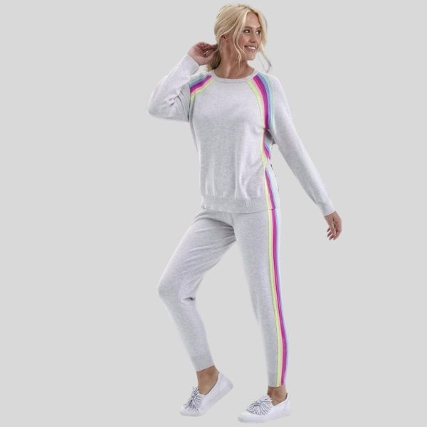 A woman wears a white jogging suit with rainbow stripes on the shoulders and down the legs.