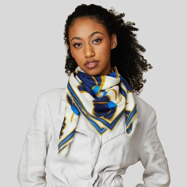 A woman wears a scarf with a blue and gold pattern around her neck..