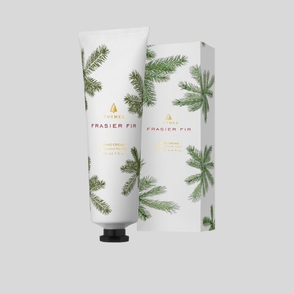 A tube of Frasier Fir hand cream is shown in front of its box, which features green fir needles.,