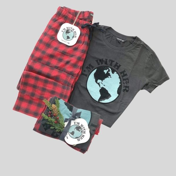 """A pair of pyjamas is shown. The T-shirt reads: """"I'm With Her"""" and shows a picture of the globe. The pants are red and black checked."""