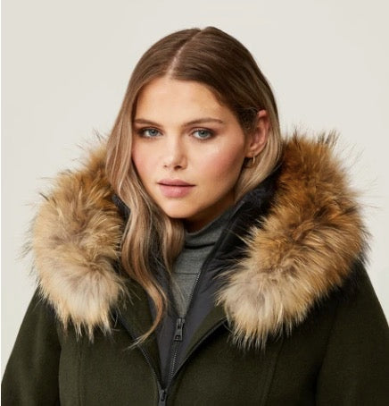 In the photograph, a woman wears a parka with a fur lined hood.