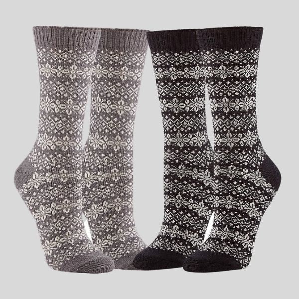 Two pairs of socks are shown. They have a snowflake design. The pair on the left is grey with white snowflakes, and the pair on the right is black with white snowflakes..