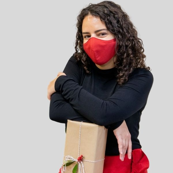 A woman wears a red mask. She holds a wrapped Christmas gift.