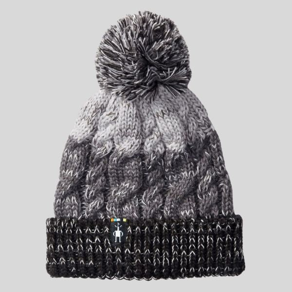 A pompom toque is shown. It has three stripes. The top is light grey, the middle is dark grey, and the band of the hat is heathered black. It has a pompom.
