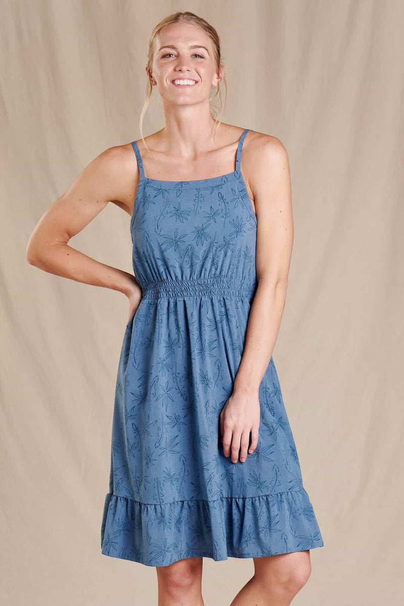 A woman wears a blue sun dress with thin straps. It has an elastic waist and a three inch ruffle at the hum.