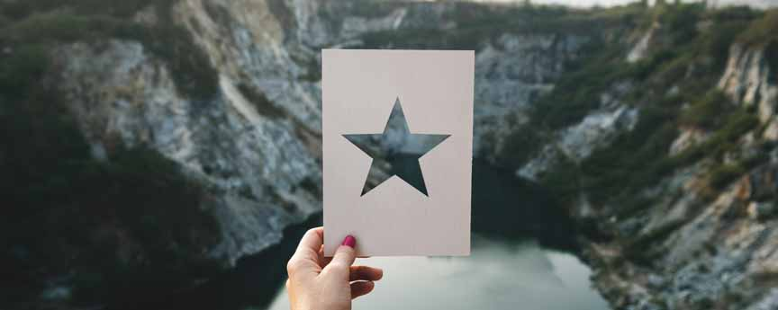 A star-shaped cut-out paper with mountain background