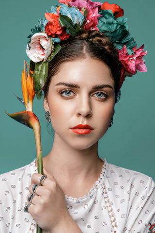 Model wears the Katmeleon Jewellery Chameleon Silver Ring and Monstera Stud Earrings while holding a strelitzia