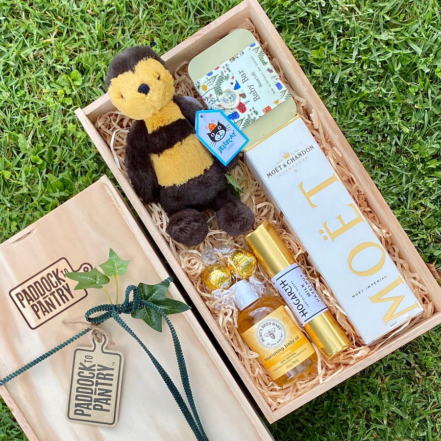 This Baby Gift Basket features a Jellycat Bee, Moët, Hogarth chocolate log, Anoint baby bar & Burt's Bees Baby Oil