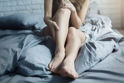 Legs of a girl sitting in bed